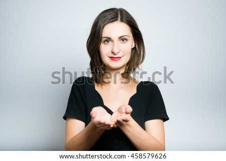 slim girl showing something on the palm, studio photo isolated on a gray background