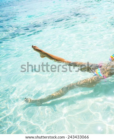 Slim hot sexy tanned skin leg woman Swimming Bikini Swimmer Cute young adult girl lie on back in blue water texture with shadow on white sand bottom Sun light in perspective ocean or sea