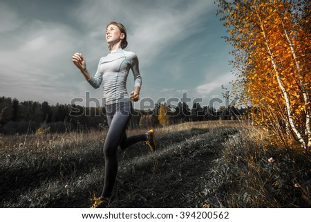 Slim lady running in the autumn forest - stock photo
