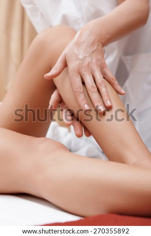 Slim legs. Close-up of a masseuse massaging legs of a young woman in spa center