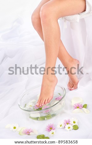 Slim legs in aromatherapy bowl, composition sided - stock photo