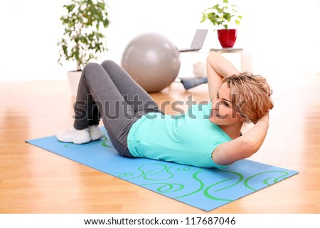 slim mid aged woman do her fitness exercises at home - stock photo