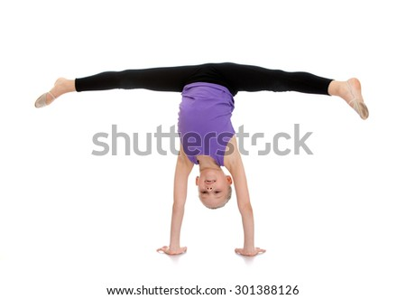 Slim pretty young girl athlete with hair combed into a ball is on your hands and do the splits. The girl is dressed in blue shirt and black tights sports-Isolated on white background - stock photo