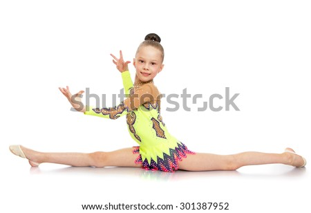 Slim pretty young girl athlete with hair combed into a ball sitting on the splits. A girl dressed in a beautiful sport swimsuit-Isolated on white background - stock photo