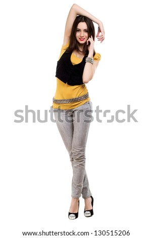 Slim smiling brunette in grey jeans, yellow t-short and black vest. Isolated on white - stock photo