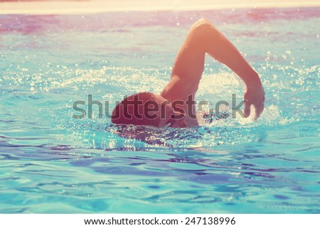 Slim sportsman swimming in a pool. - stock photo