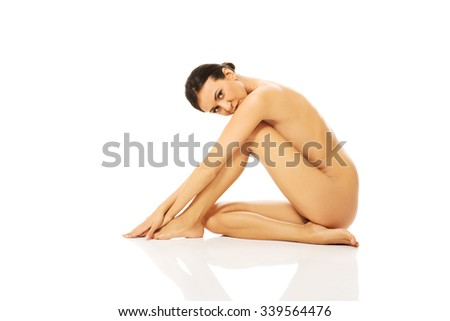 Slim tanned woman sitting touching her foot