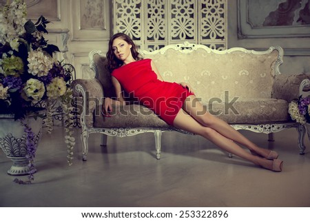 Slim trendy, luxurious, fashion woman in  lux vintage interior. Girl in red short dress on a luxury background - stock photo