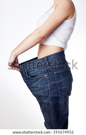 Slim waist of young woman in big jeans showing successful weight loss. - stock photo