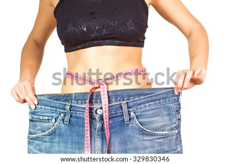 Slim Waist of Young Woman with perfect healthy thin body,showing her old jeans after successful diet. Unrecognizable person.Weight loss and slimming concept.