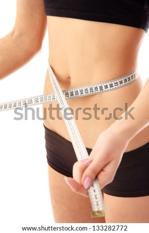 Slim waist with a tape measure around it - stock photo