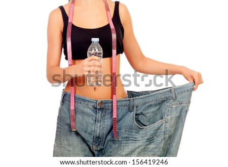 Slim woman back with huge pants and water bottle isolated on white background - stock photo