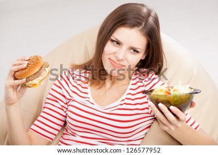 Slim woman choosing between a salad and hamburger - stock photo