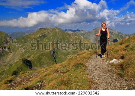 Slim woman hiker on sunny mountain trail  - stock photo