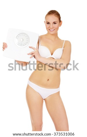 Slim woman holding a scales - stock photo