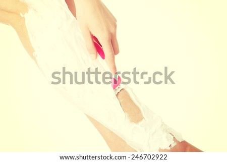 Slim woman is shaving her legs with foam and razor.  - stock photo
