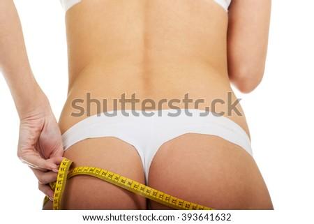 Slim woman measuring her butt. - stock photo
