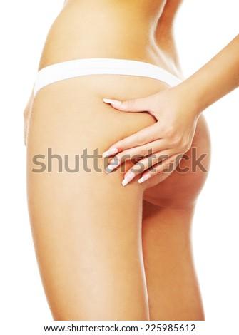 Slim woman measuring her fat - stock photo