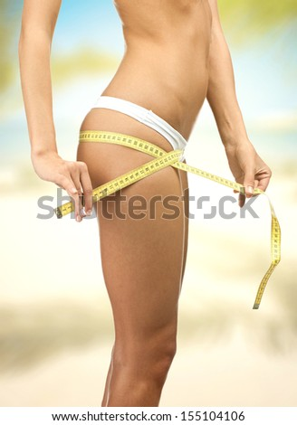 Slim woman measuring perfect shape of her hips