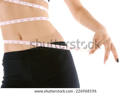 Slim woman measuring waist with measurement tape isolated on white background - stock photo