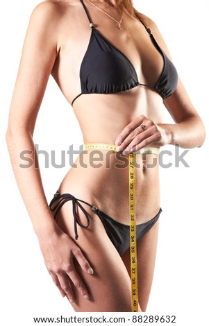 slim woman measuring waist with tape measure in centimeters isolated over white background - stock photo
