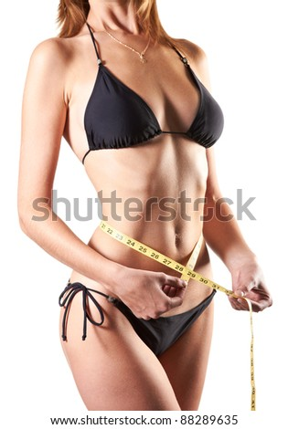 slim woman measuring waist with tape measure in inches isolated over white background - stock photo
