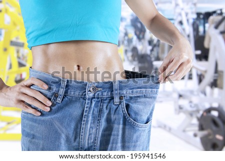 Slim woman pulling oversize jeans. Weight loss concept. - stock photo