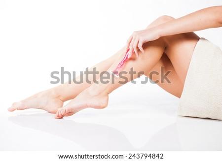 Slim woman shaving legs with pink razor - stock photo