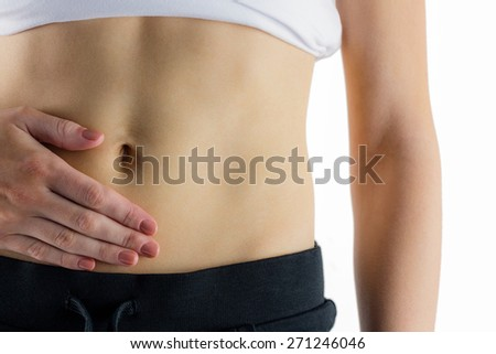 Slim woman touching her belly on white background
