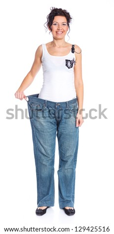 Slim woman trying large jeans after diet. Isolated white background - stock photo