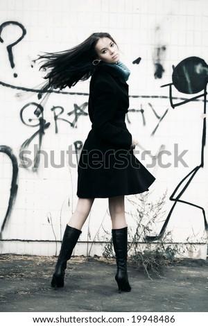 Slim woman turning back on graffiti wall background. - stock photo