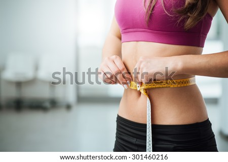 Slim young woman measuring her thin waist with a tape measure, close up - stock photo