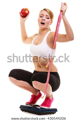 Slimming diet weight loss. Upset unhappy sad young woman girl with measuring tape on weighing scale holding apple. Healthy lifestyle concept. Isolated on white background. - stock photo