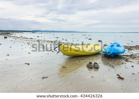 slippers and Kayak on the beach - stock photo