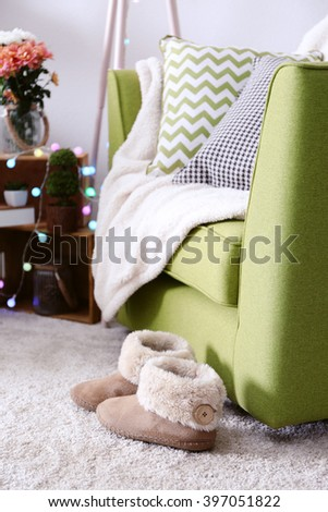 Slippers near armchair in interior of living room - stock photo