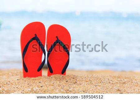 Slippers on beach - stock photo