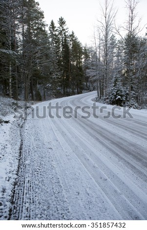 Slippery and snow road curving right on a cold winter morning. Image taken during sunrise after the first snow covered up the ground. It's mandatory to wear winter tires in Finland in winter time. - stock photo