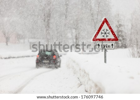 Slippery driving conditions in winter, sign - stock photo