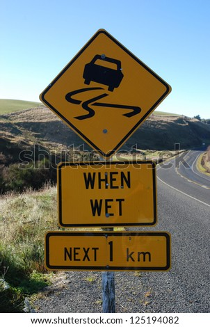 Slippery when wet roadsign in New Zealand - stock photo