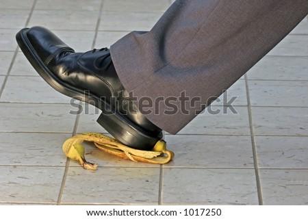 slipping and falling on a banana peel - stock photo