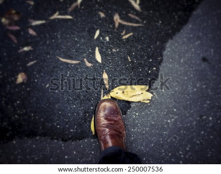Slipping on a banana; first person perspective of a shoe stepping on a banana peel. - stock photo