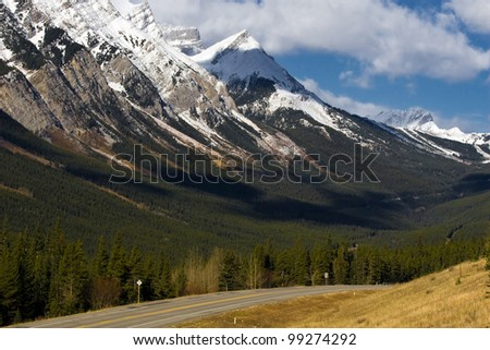 Slopes of Canadian Rockies on background with road and pine forest - stock photo