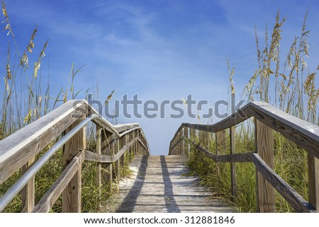 Sloping old wooden boardwalk viewed as walking uphill over grassy dunes to the beach.
