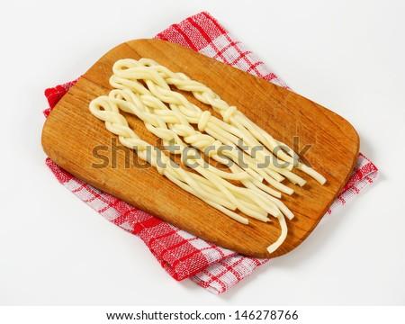 Slovak string cheeses Korbacik on wooden cutting board - stock photo
