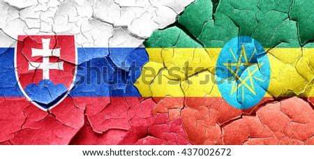Slovakia flag with Ethiopia flag on a grunge cracked wall - stock photo