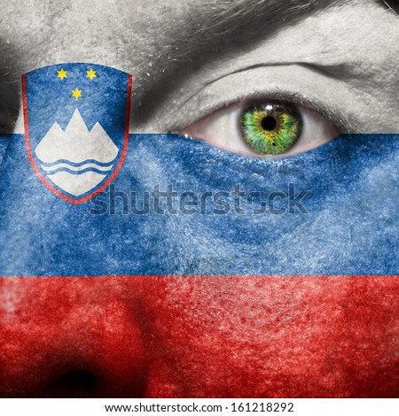 Slovenia flag painted on a man's face with green eye to show Slovenia,support