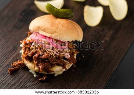 Slow cooked pulled pork with BBQ sauce, pickled onions, coleslaw and cheese served in a hamburger bun with dill pickle and chips as sides. It's a messy sandwich but so delicious! - stock photo