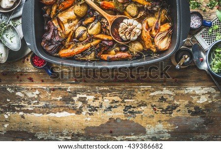 Slow cooked rabbit stew with  forest mushrooms and garden vegetables of season. Rabbit ragout on rustic kitchen table with cooking ingredients and tools, top view, border. Country food - stock photo