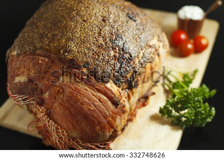 Slow cooked roast beef  covered with mustard sauce, baby tomatoes and garlic sauce on black reflective surface - stock photo