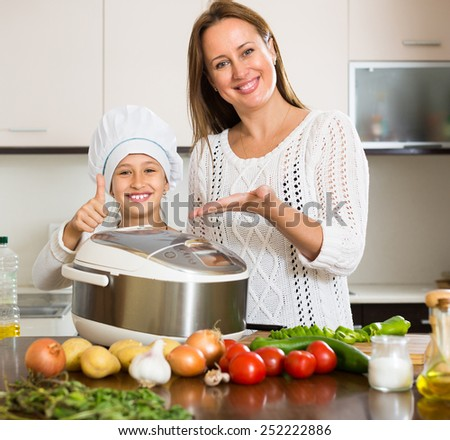 Slow cooker helping mother and smiling girl to prepare dinner at home kitchen - stock photo